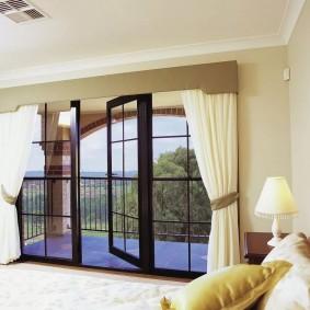 Rideaux blancs sur la fenêtre avec une porte de balcon