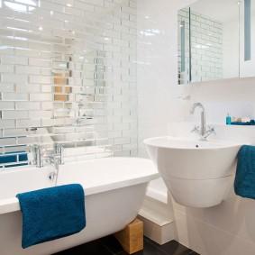 Serviette bleue sur le rebord d'une baignoire blanche