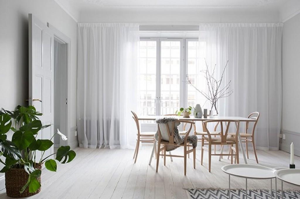 Rideaux de tulle blanc sur une fenêtre de salon de style scandi