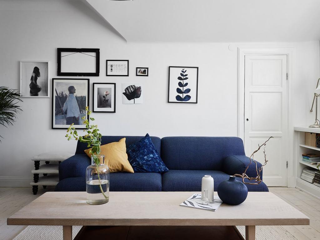Canapé bleu sur fond de murs blancs du salon