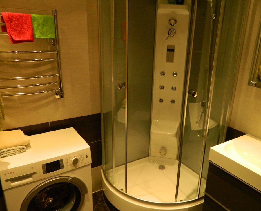 Cabine de douche compacte dans la salle de bain avec machine à laver