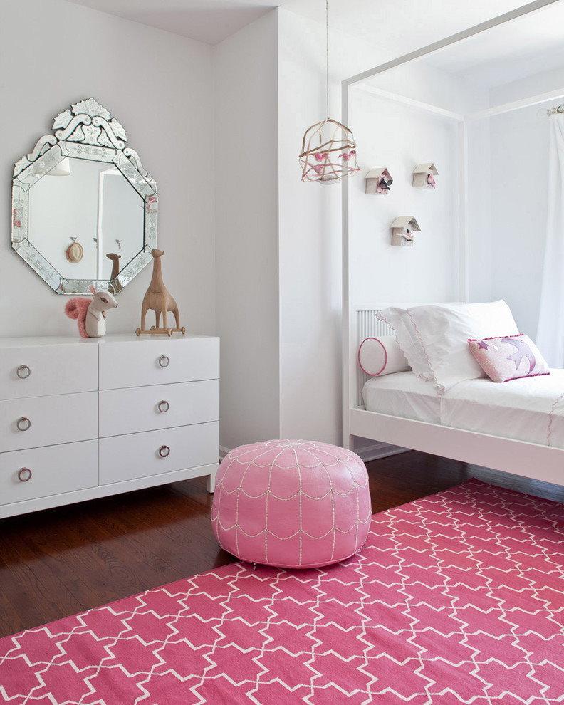 Tapis rose dans une chambre avec une commode blanche