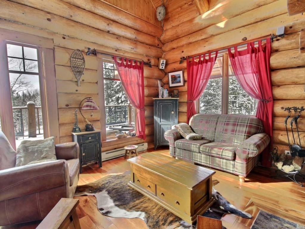 Rideaux roses sur les fenêtres d'une cabane en rondins