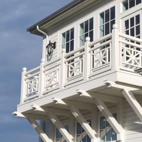 Balcon blanc sur la façade d'une maison en bois