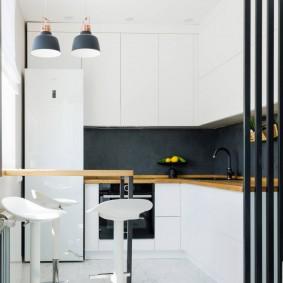 Tablier noir dans une cuisine blanche