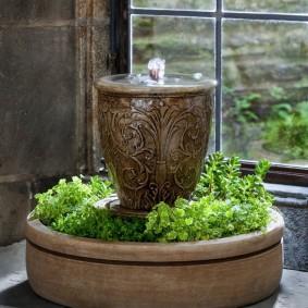 Fontaine décorative avec des plantes vivantes sur le rebord de la fenêtre de l'appartement