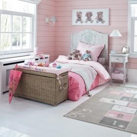 Poitrine en osier devant un lit d'enfant