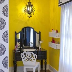 Coiffeuse noire sur fond de mur jaune