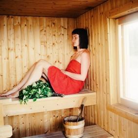 Fille sur des étagères dans un sauna finlandais