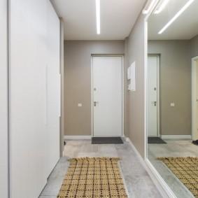 Un immense miroir dans le couloir d'un appartement de deux chambres