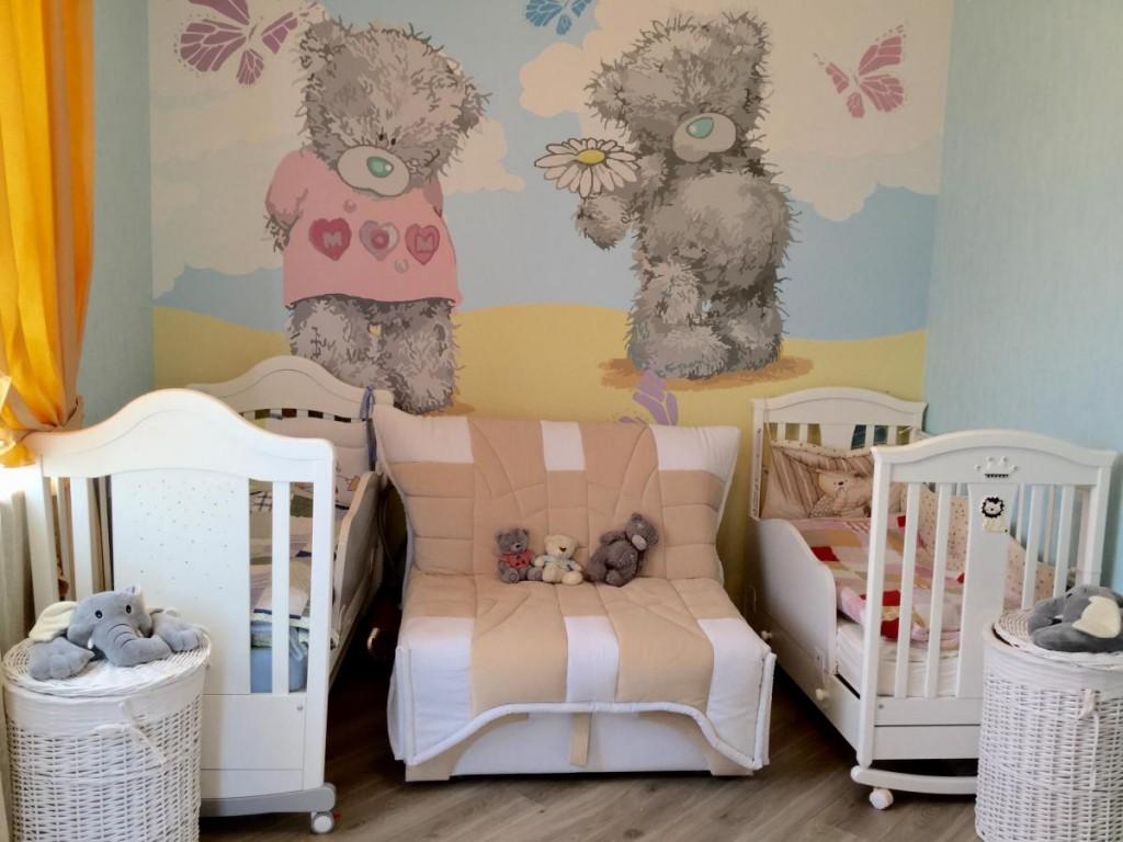 Des lits dans la chambre avec des ours sur le papier peint