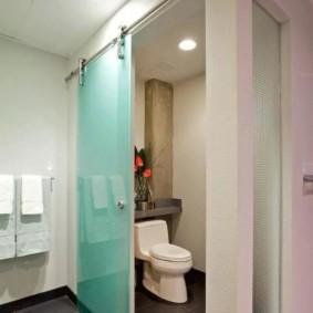 Toilettes au sol derrière une cloison vitrée