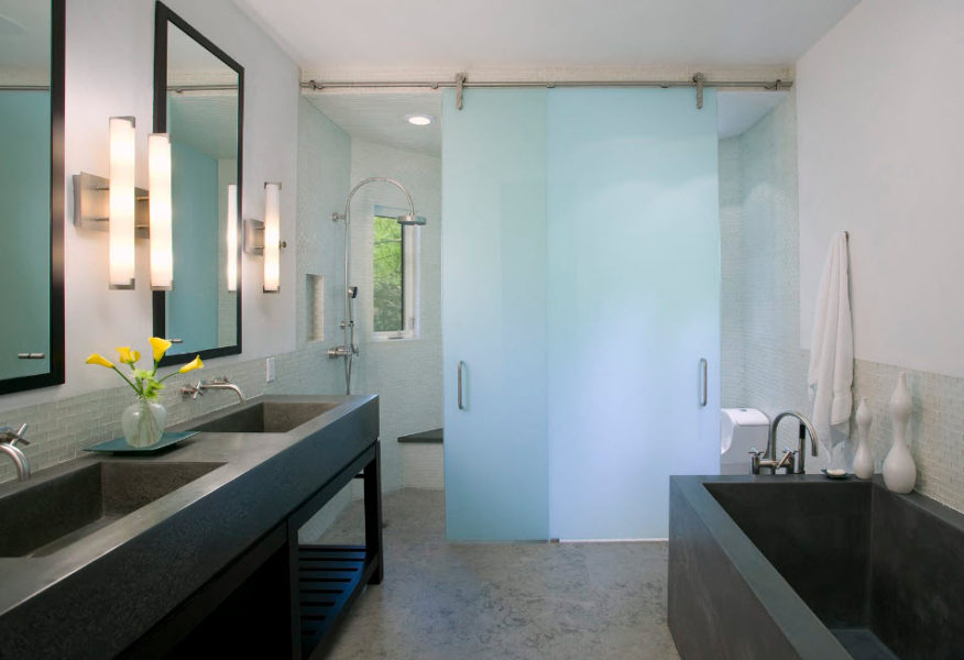 Portes coulissantes en verre dans une salle de bain spacieuse