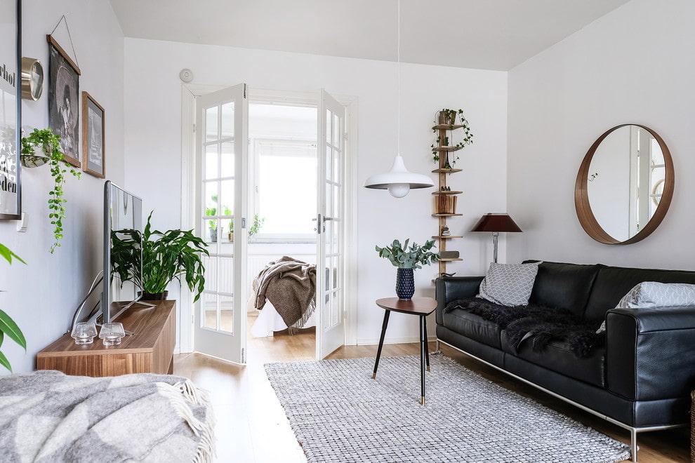 Canapé noir dans un salon de plain-pied blanc