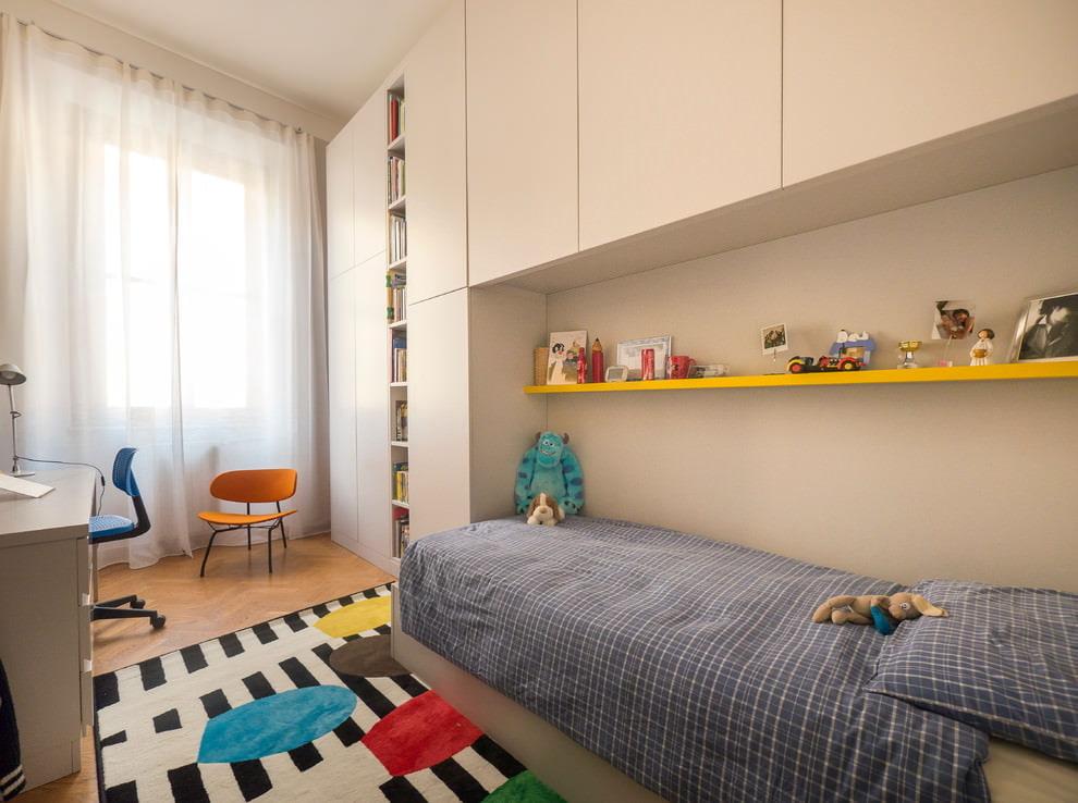 Étagère jaune sur lit gris pour enfants